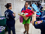 18 SEPTEMBER 2017 - BANGKOK, THAILAND: A volunteer gives flip flops and food to people at Poh Teck Tung in Bangkok on the last day Hungry Ghost Month. The Ghost Festival, also known as the Hungry Ghost Festival, Zhongyuan Festival or Yulan Festival is a traditional Buddhist and Taoist festival held in Asian countries. According to the Chinese calendar (a lunisolar calendar), the Ghost Festival is on the 15th night of the seventh month. In Chinese culture, the fifteenth day of the seventh month in the lunar calendar is called Ghost Day and the seventh month in general is regarded as the Ghost Month, in which ghosts and spirits, including those of the deceased ancestors, come out from the lower realm. Distinct from both the Qingming Festival (in spring) and Double Ninth Festival (in autumn) in which living descendants pay homage to their deceased ancestors, during Ghost Festival, the deceased are believed to visit the living.     PHOTO BY JACK KURTZ