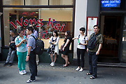 Summertime in London, England, UK. Scene in Chinatown. The present Chinatown is in the Soho area occupying the area in and around Gerrard Street. It contains a number of Chinese restaurants, bakeries, supermarkets, souvenir shops, and other Chinese-run businesses and is in itself a major tourist destination. Here Chinese tourists gather outside Won Kei restaurant. Won Kei's was made famous for it's rude waiting staff.