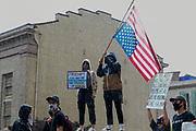 A protester waves an upside down American flag at a protest honoring George Floyd who was killed by police on Memorial Day in Minneapolis MN