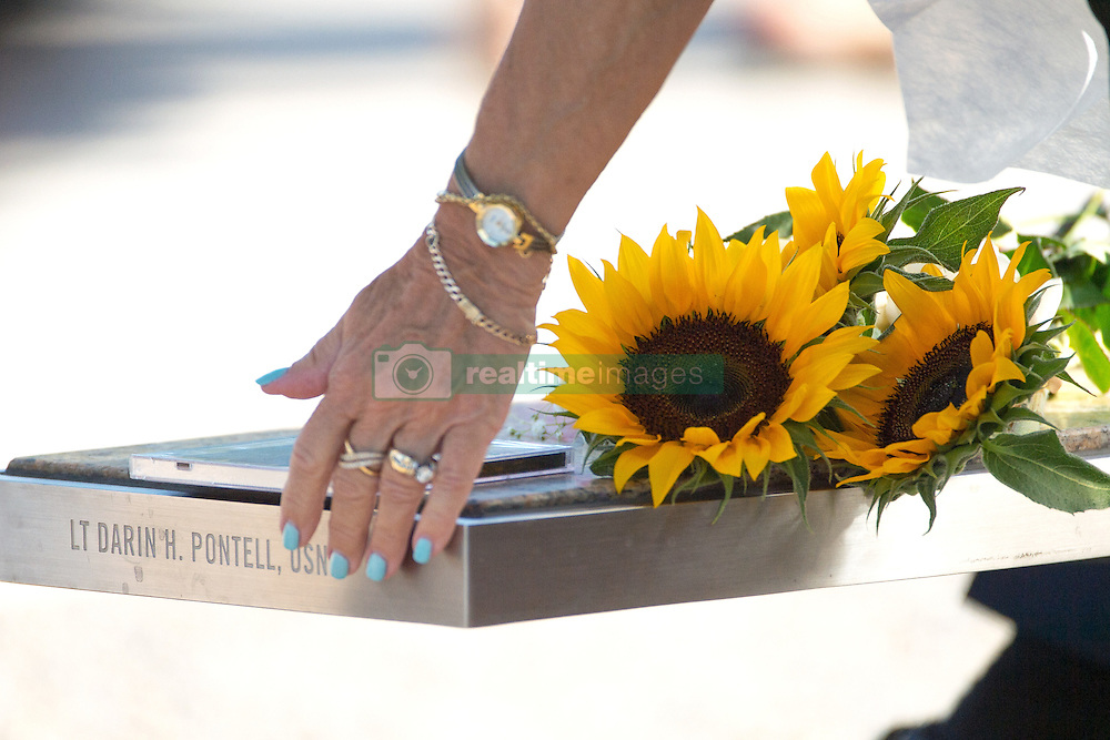September 11, 2016 - Arlington, United States of America - A woman runs her hand along a bench dedicated to Navy Lt. Darin H. Pontell at the National 9/11 Pentagon Memorial following a remembrance ceremony commemorating the 15th anniversary of the 9/11 terrorist attacks at the Pentagon September 11, 2016 in Arlington, Virginia. (Credit Image: © Ej Hersom/Planet Pix via ZUMA Wire)