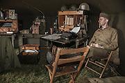 USA, Oregon, Astoria, Ft. Stevens State Park, living historian relaxing in HQ tent, WWII living history encapment. MR