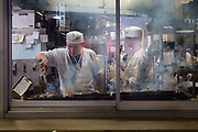 A chef working on the grill cooking yakitori seen through a steamed up window in Shibuya.