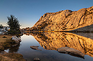 Alpenglow at sunset on Fletcher Peak reflected in Vogelsang Lake; Yosemite National Park; California