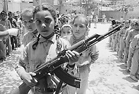 1970, Beirut, Lebanon --- Young girl holding a machine gun, with other children in training as commandos, at a Palestinian refugee camp which gave strong support to Al Fatah, the pre-PLO (Palestine Liberation Organization) group of which Yassir Arafat was the leader. --- Image by © Owen Franken
