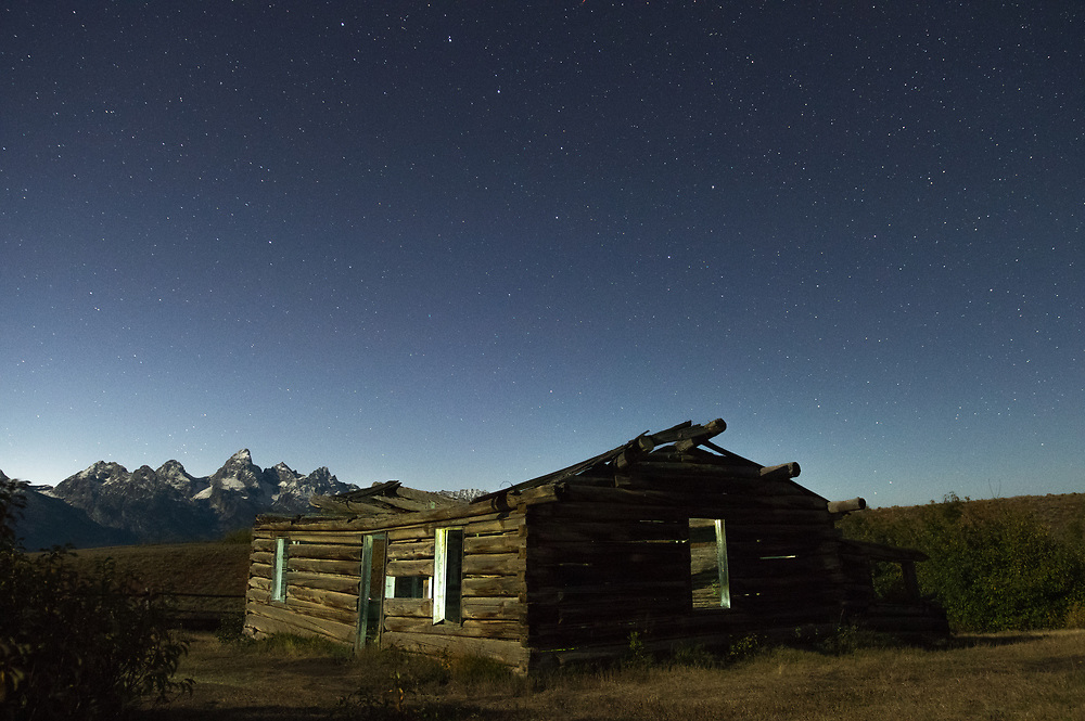 An old derelict homesteader cabin home sits under a lonely starlit sky with the Grand Teton mountains of Wyoming in the distance.