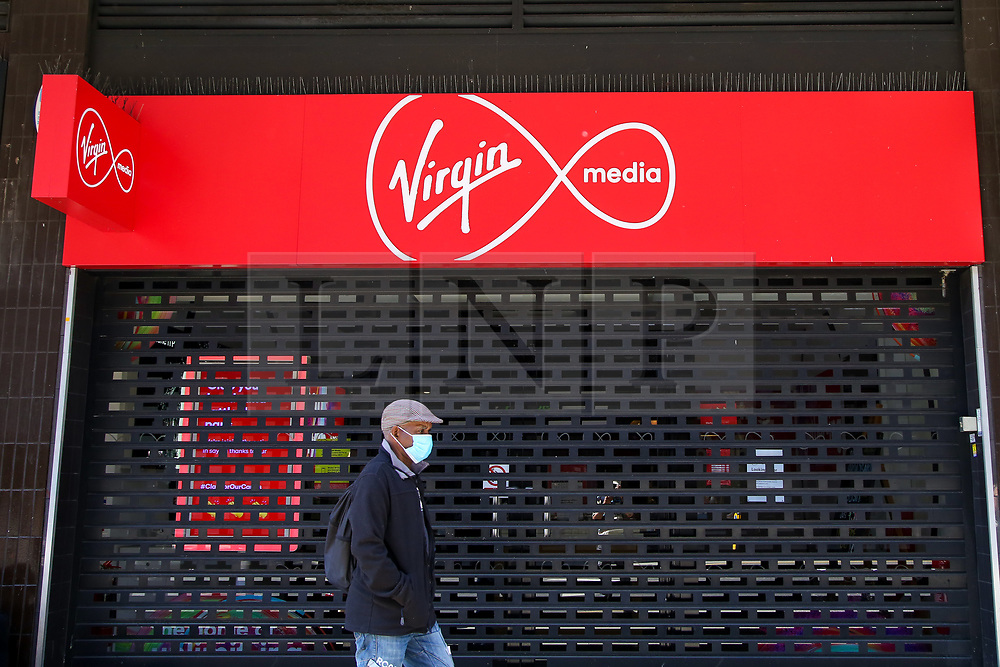 © Licensed to London News Pictures. 01/06/2020. London, UK. A man wearing a face covering walks past a branch of Virgin Media in Wood Green, north London. All 53 Virgin Media stores closed in March due to COVID-19 lockdown and according to the firm none of the high street shops will reopen once restrictions are lifted this month. Photo credit: Dinendra Haria/LNP