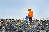 Mother and toddler exploring rocky shorline on a rainy day in Seward, Alaska.