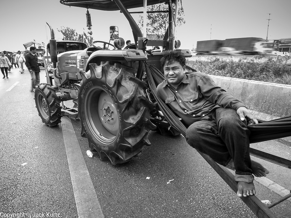 21 FEBRUARY 2014 - KHLONG CHIK, PHRA NAKHON SI AYUTTHAYA, THAILAND:  A farmer relaxes in a hammock strung between his tractor and a wagon he was pulling. About 10,000 Thai rice farmers, traveling in nearly 1,000 tractors and farm vehicles, blocked Highway 32 near Bang Pa In in Phra Nakhon Si Ayutthaya province. The farmers were traveling to the airport in Bangkok to protest against the government because they haven't been paid for rice the government bought from them last year. The farmers turned around and went home after they met with government officials who promised to pay the farmers next week. This is the latest blow to the government of Yingluck Shinawatra which is confronting protests led by anti-government groups, legal challenges from the anti-corruption commission and expanding protests from farmers who haven't been paid for rice the government bought.   PHOTO BY JACK KURTZ