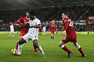 Wilfried Bony of Swansea city © shields the ball from Andrew Robertson ® and Emre Can of Liverpool (l). Premier league match, Swansea city v Liverpool at the Liberty Stadium in Swansea, South Wales on Monday 22nd January 2018. <br /> pic by  Andrew Orchard, Andrew Orchard sports photography.