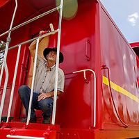 Grants city councilor Michael Lewis paints the trim on a newly-restored caboose at Fire and Ice Park in Grants Friday.