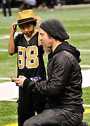"NFL Saints -Actor Brad Pitt and his adopted son Maddox, Maddox looks at Brads blackberry after Brad took his photo and then they sent it to his mom Angelina Jolie while on the sidelines before teh game. walk on the New Orleans Saints side line before the NFC playoff game between the Saints and the Cardinals Saturday jan. 16, 2010 in Louisiana at the SuperDome. Brad has been instrumental in rebuilding the lower ninth ward in New Orleans through his Make it Right non profit that is building ""green homes"" where Hurricane Katrina destroyed everything. The Saints beat the Cardinals to advance in the playoffs. Photo ©Suzi Altman/Suzisnaps.comNFL Saints -Cardinals playoffs. Photo ©Suzi Altman/Suzisnaps.comNFL Saints -Cardinals playoffs. Photo ©Suzi Altman/Suzisnaps.com"