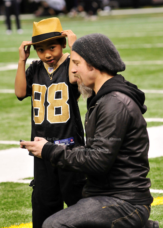"""NFL Saints -Actor Brad Pitt and his adopted son Maddox, Maddox looks at Brads blackberry after Brad took his photo and then they sent it to his mom Angelina Jolie while on the sidelines before teh game. walk on the New Orleans Saints side line before the NFC playoff game between the Saints and the Cardinals Saturday jan. 16, 2010 in Louisiana at the SuperDome. Brad has been instrumental in rebuilding the lower ninth ward in New Orleans through his Make it Right non profit that is building """"green homes"""" where Hurricane Katrina destroyed everything. The Saints beat the Cardinals to advance in the playoffs. Photo ©Suzi Altman/Suzisnaps.comNFL Saints -Cardinals playoffs. Photo ©Suzi Altman/Suzisnaps.comNFL Saints -Cardinals playoffs. Photo ©Suzi Altman/Suzisnaps.com"""
