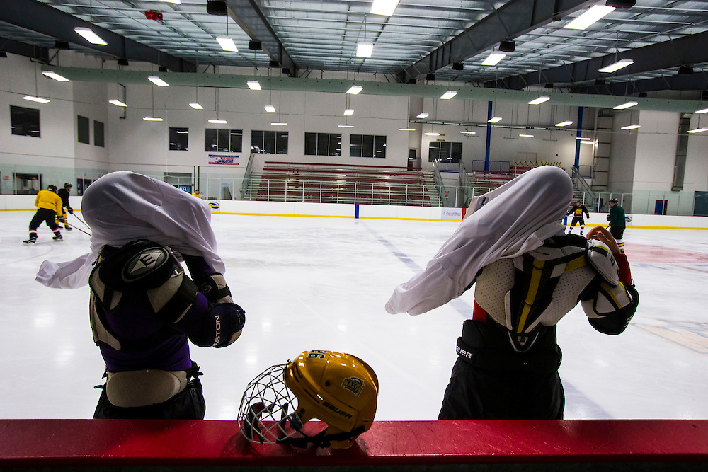 George Mason forward, Seve Cordova, (L) and forward Dylan Talbot exchange warm up jersey before the start of practice at Prince William Ice Rink in Woodbridge, VA on January 22, 2014. Cordova had grab Talbot's warm up jersey on accident in the locker room.