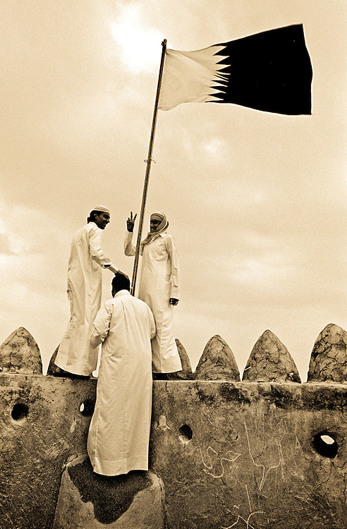 Three Qatari youth's under the countries flag in the Al Zubara fort on the Northwest coast of Qatar. Built in 1938 during the reign of Skeikh Abdullah Bin Qassim Al Thani. Now a museum and tourist attraction. Qatar, Middle East