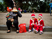 24 DECEMBER 2017 - HANOI, VIETNAM: Brothers in Santa Claus suits on a street in the old quarter of Hanoi. The commercial and gift giving aspect of Christmas is widely celebrated in Vietnam and Vietnam's 5+ million Catholics celebrate the religious aspects of Christmas.     PHOTO BY JACK KURTZ