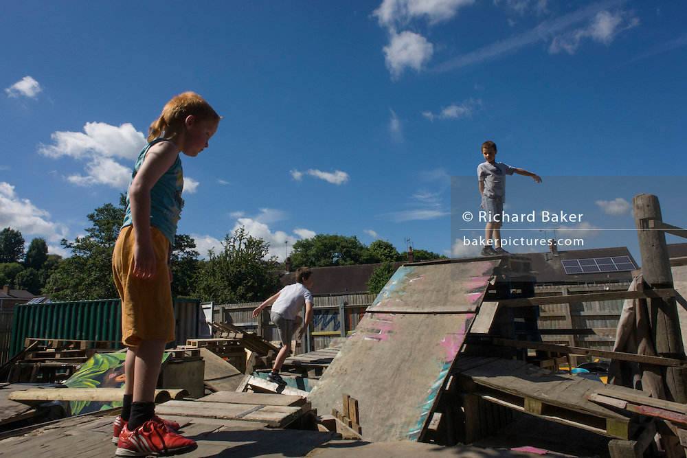 Children play on old crates and pallets in risk averse playground called The Land on Plas Madoc Estate, Ruabon, Wrexham, Wales. <br /> <br /> From the chapter entitled 'Playing with Fire' from the book 'Risk Wise: Nine Everyday Adventures' by Polly Morland (Allianz, The School of Life, Profile Books, 2015).