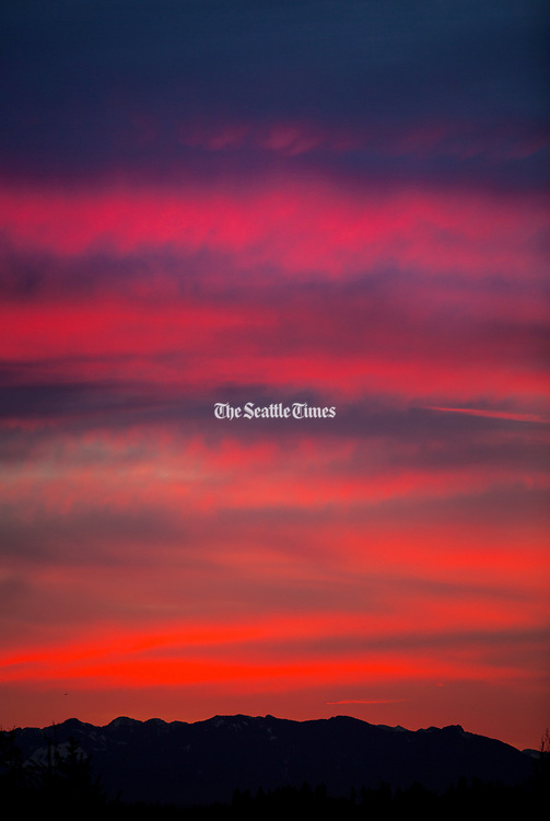 A winter sunrise over the Cascade Mountain range lights up the cloudy skies in this view from the Horizon View neighborhood of Lake Forest Park in the morning. (Mike Siegel / The Seattle Times)
