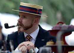 © Licensed to London News Pictures. 07/07/2012. London, UK A man smokes a pipe whilst wearing a straw boater at 'The Chap's Olympiad' in central London on July 7th, 2012. 'The Chap' is a light-hearted magazine, aimed at revisiting the fashions and pastimes of the polite aspects of 1920's to 1950's England. The annual Olympiad event sees competitors take part in events such the 'Cucumber Sandwich Discus', 'The Umbrella Joust' and 'The Tug of Hair'e. Photo credit : Stephen Simpson/LNP