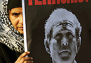 Islamic woman weeping behind a poster of US President George W. Bush during an anti-war demonstration held in central London, UK, on Saturday, March 19, 2005. **ITALY OUT**