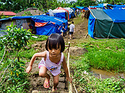 29 JANUARY 2018 - SANTO DOMINGO, ALBAY, PHILIPPINES: A girl leaves an impromptu camp in Santo Domingo for people evacuated from their homes because of the Mayon volcano. Many of the shelters in Santo Domingo are filled beyond capacity and people are sleeping tents and huts along the roads.  Mayon volcano's eruptions continued Monday. At last count, more 80,000 people have been evacuated from their homes of the slopes of the volcano and are crowded into shelters in communities outside of the danger zone.    PHOTO BY JACK KURTZ
