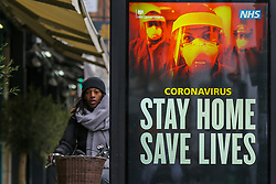 © Licensed to London News Pictures. 10/01/2021. London, UK. A woman without wearing a protective face covering walks past the Government's 'Stay Home, Save Lives' Covid-19 publicity campaign poster in north London, as the number of cases of the mutated variant of the SARS-Cov-2 virus continues to spread around the country. Almost 60,000 new cases of coronavirus were reported in the UK on Saturday 9 January 2021 and the number of deaths after a positive test passed 80,000, since the pandemic began.  Photo credit: Dinendra Haria/LNP