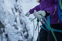 Female climber threads rope through hands in winter, Lofoten Islands, Norway