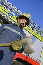Part time male firefighter standing in front of fire engine holding fire axe,