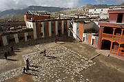 """Monks and Lamas fill the courtyard of the Sakyama Monastic School following morning prayer in Lo Manthang, the capital of the """"Forbidden Kingdom"""" of Lo in the upper Mustang Region of Nepal. (Photo by David Stubbs)"""