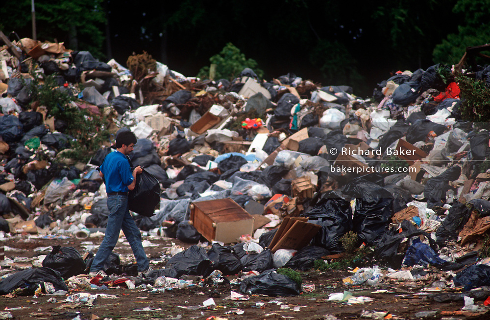 A resident of Liverpool takes his refuse to Allerton Park during the Liverpool binmens' strike of 1991, on 14th June 1991, in Liverpool, Merseyside, England. The industrial action against the local authority was a health problem for Liverpool over that summer when streets filled with rubbish. Vermin like rats ran around and public city parks filled with every kind of refuse and garbage. Few of these back-to-backs existed in the 1990s after being cleared to allow construction of high-rise tower-blocks and flats. (Photo by Richard Baker / In Pictures via Getty Images)