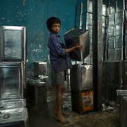 A young boy halts from his work stacking up repaired and cleaned cooking oil cans in Dharavi's recycling area.