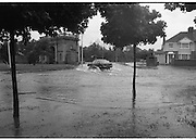 """Flooding at the Dodder..1986..26.08.1986..08.26.1986..28th August 1986..As a result of Hurricane Charly (Charlie) heavy overnight rainfall was the cause of severe flooding in the Donnybrook/Ballsbridge areas of Dublin. In a period of just 12 hours it was stated that 8 inches of rain had fallen. The Dodder,long regarded as a """"Flashy"""" river, burst its banks and caused great hardship to families in the 300 or so homes which were flooded. Council workers and the Fire Brigades did their best to try and alleviate some of the problems by removing debris and pumping out some of the homes affected..Note: """"Flashy"""" is a term given to a river which is prone to flooding as a result of heavy or sustained rainfall...A motorist manages to get through the worst of the flood water at the junction."""