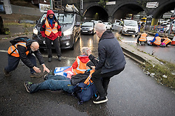© Licensed to London News Pictures. 01/10/2021. London, UK. An angry motorist attempts to drag a protester off the road. Climate protest group Insulate Britain block the M1 at the junction with the North Circular at Staples Corner in North London. Insulate Britain have successfully blocked various roads around the capital over a number of weeks, resulting in a court injunction banning them from going near the M25 motorway. Photo credit: Ben Cawthra/LNP