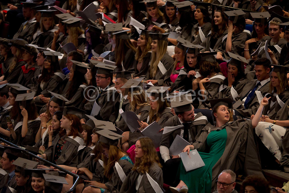 Young graduates wearing rented gowns and mortarboards sit in the central hall of their university, waiting for their graduation ceremony to start, on 13th July 2017, at the University of York, England.