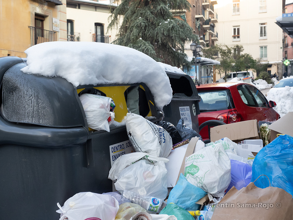 Madrid, Spain. 14th January, 2021. A pile of trash bags pile on a recycling dumpster. Madrid's municipal cleaning services are working partially after storm Filomena, works are focused on clearing the streets but trash removal services are not fully operative. © Valentin Sama-Rojo.