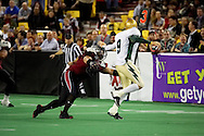4/12/2007 - Dustin Almond (9) holds back the oncoming Wild player, Atonio Lolesio (51) in the 46-33 Frisco Thunder victory over the Alaska Wild in the first professional football game in Alaska.