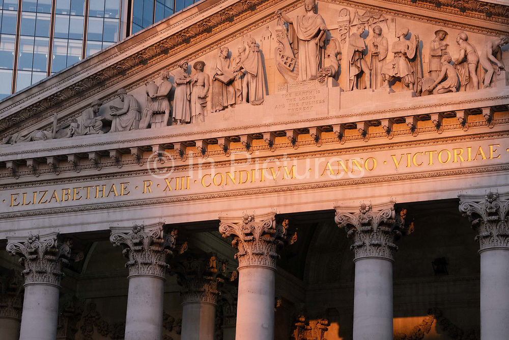 With modern offices of financial institutions behind, an architectural sunlit view of the friezes and Latin inscriptions on the pediment of the Royal Exchange in the City of London, the capitals financial district, on 27th February 2021, in London, England. At the top of Doric and Ionic columns with their ornate stonework, powerfully strong lintels cross, bearing the load of fine artistry and carvings which feature the design by Sir William Tite in 1842-1844 and opened in 1844 by Queen Victoria whose name is written in Latin Victoriae R. It's the third building of the kind erected on the same site. The first Exchange erected in 1564-70 by sir Thomas Gresham but was destroyed in the great fire of 1666. It's successor, by Jarman, was also burned down in 1838. The present building is grade 1 listed and cost about £150,000.