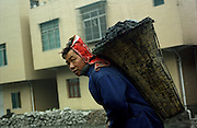 A coal miner in Wangjiazhai, South West China, working over-ground mining. Coal miners carry up to 50kg of coal on their back. They are paid by the amount of buckets they fill and carry.