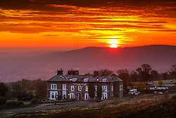 © Licensed to London News Pictures. 19/10/2020. Ilkley UK. The sky glows red as the sun rises this morning over the Cow & Calf pub on Ilkley moor in Yorkshire as the UK expects heavy rain & gales this week. Photo credit: Andrew McCaren/LNP