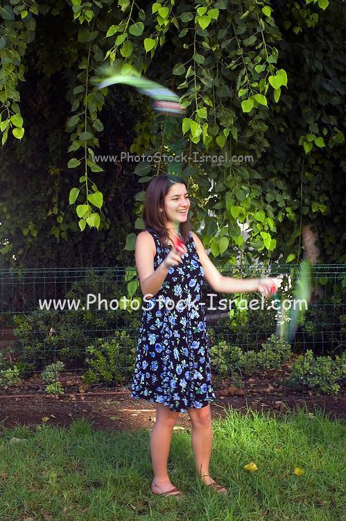 A Young female teen, 18 years old, spinning Pois in a park