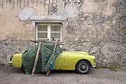 an old MG sport car under a tarp