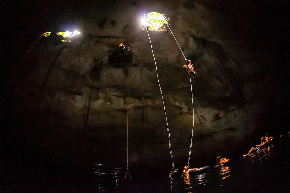 People rappelling into a cenote, a large limestone sinkhole which is part of the world's longest underwater river, Riviera Maya, Mexico