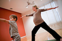 """8 Novembre, 2008. Brooklyn, New York.<br /> <br /> Kristen Mangoven e suo figlio Mikel, 3 anni,  seguono un corso di yoga per famiglie con l'istruttrice Ute Kirchgaessner al Bend & Bloom Yoga a Park Slope, Brooklyn, NY. Park Slope, spesso definito dai newyorkesi come """"The Slope"""", è un quartiere nella zona ovest di Brooklyn, New York, e confinante con Prospect Park.  Park Slope è un quartiere benestante che ha il maggior numero di nascite, la qualità della vita più alta e principalmente abitato da una classe media di razza bianca. Per questi motivi molte giovani coppie e famiglie decidono di trasferirsi dalle altre municipalità di New York a Park Slope. Dal punto di vista architettonico, il quartiere è caratterizzato dai brownstones, un tipo di costruzione molto frequente a New York, e da Prospect Park.<br /> <br /> ©2008 Gianni Cipriano for The New York Times<br /> cell. +1 646 465 2168 (USA)<br /> cell. +1 328 567 7923 (Italy)<br /> gianni@giannicipriano.com<br /> www.giannicipriano.com"""