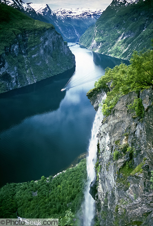 """A ferry cruises by a waterfall on Geirangerfjord, the epitome of Norwegian fjords. Geirangerfjorden (the Geiranger fjord) is a stunningly beautiful 15-kilometer (9.3-mile) long branch of Storfjord (Great Fjord, the fifth longest in Norway). Geirangerfjord is one of Norway's most visited tourist sites and has been listed as a UNESCO World Heritage Site since 2005. Take the car ferry for an impressive sightseeing trip between Geiranger and Hellesylt, in Stranda municipality, Sunnmøre region, Møre og Romsdal county, Norway. Published on the cover of Wells Fargo Lifescapes magazine August 2012. Published in """"Light Travel: Photography on the Go"""" book by Tom Dempsey 2009, 2010."""
