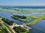 """Nederland, Overijssel, Gemeente Kampen; 21–06-2020; Reevesluis en monding van het Reevediep in het Revemeer (voorheen Drontermeer).<br /> Het Reevediep is aangelegd in het kader van het project Ruimte voor de Rivier om bij hoogwater water af te voeren voordat dit het nabij gelegen Kampen bereikt, direct naar het IJsselmeer, de 'bypass Kampen'. Het Reevediepgebied is ook een natuurgebied en vormt een ecologische verbindingszone tussen rivier de IJssel en Drontermeer.<br /> Mouth of the Reevediep en Reeve lock.<br /> The Reevediep has been constructed as part of the Room for the River project, and functions to discharge high waters before reaching the nearby Kampen, directly to the IJsselmeer, the """"bypass Kampen"""". The Reevediep area is also a nature reserve and forms an ecological connecting zone between the river IJssel and Drontermeer.<br /> <br /> luchtfoto (toeslag op standaard tarieven);<br /> aerial photo (additional fee required)<br /> copyright © 2020 foto/photo Siebe Swart"""