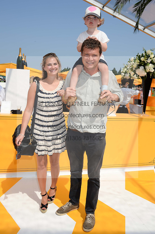 JACK KIDD and CALLIE MOORE with their son JESSE KIDD at the Veuve Clicquot Gold Cup, Cowdray Park, Midhurst, West Sussex on 21st July 2013.