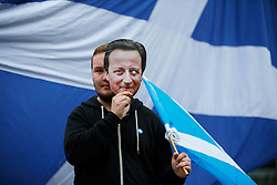 © Licensed to London News Pictures. 19/09/2014. Glasgow, UK. A disappointed 'Yes' campaigners reacting to Scotland's decision to stay in the union with a David Cameron mask at George Square in Glasgow on Friday, 19 September 2014, after the Scottish independence referendum. Photo credit : Tolga Akmen/LNP