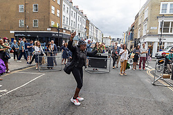 Licensed to London News Pictures. 27/08/202. London, UK. A busy Portobello Road and market in Notting Hill, west London today with people dancing in the street to live music as the 2021 Notting Hill Carnival is cancelled for another year as a result of the ongoing Covid-19 pandemic. However, there is expected to be alternative events going on for Londoners and tourists this weekend with steel bands and Brazilian bands making an appearance at the Panorama event. Photo credit: Alex Lentati/LNP
