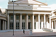 Teatro Solis Theatre in central city with imposing pillars on the facade, a small woman in black walking by. Montevideo, Uruguay, South America