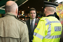 © Licensed to London News Pictures. 03/11/2015. Alum Rock, Birmingham, UK. Shadow Home Secretary ANDY BURNHAM visiting Alum Rock in Birmingham to launch the Labour Policy on Policing. Pictured, ANDY BURNHAM, centre, talking to Inspector CHRIS SMITH, right and MP JACK DROMEY, left, on the Alum Rock Road. Photo credit : Dave Warren/LNP