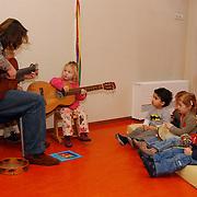 Gitarist Faarzon Morel tijdens de voorleesochtend bij de Koelemoes Huizen.kind, gitaar, juf, leraar, opvang, crache, spelen, muziek, kinderen, stoel,